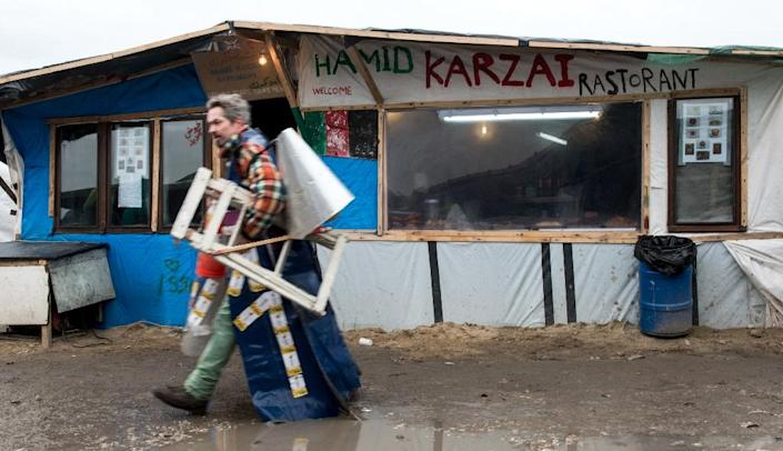 """A migrant walks past a makeshift restaurant in the so-called """"Jungle"""" migrant camp in Calais, on February 23, 2016 (AFP Photo/Denis Charlet)"""