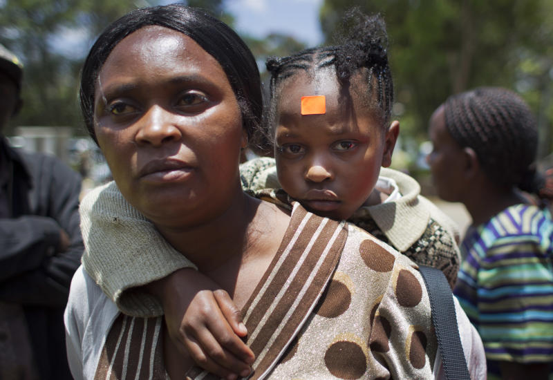 Hilda Wateri, 8, who was injured in an explosion at a Sunday school class and who wears an orange triage label on her forehead, is carried by her mother Milka Wajera to the accident and emergency wing of Kenyatta National Hospital in Nairobi, Kenya Sunday, Sept. 30, 2012. An explosive device set off in a Sunday school class killed one child and seriously wounded three, according to Nairobi's acting police chief, who said said he suspects sympathizers with the Somali militant group al-Shabab were behind the attack at the Anglican church. (AP Photo/Ben Curtis)