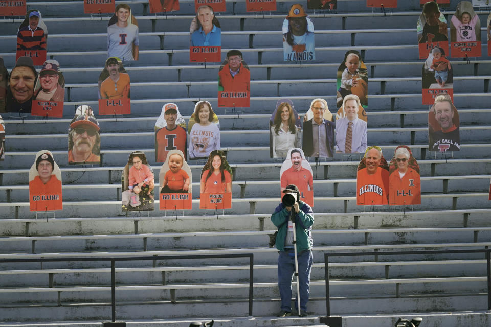 A photographer shoots pregame warmups near cardboard cutouts of fans before an NCAA college football game between Illinois and Purdue Saturday, Oct. 31, 2020, in Champaign, Ill. (AP Photo/Charles Rex Arbogast)