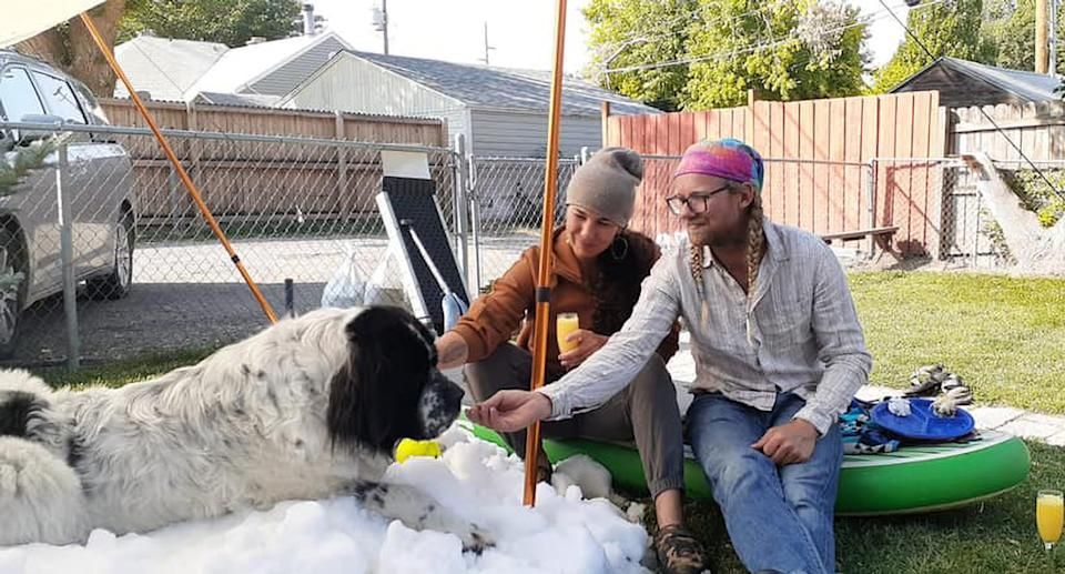 Maggie the dog, who lived in Utah, lies in the snow, flanked by her owners.