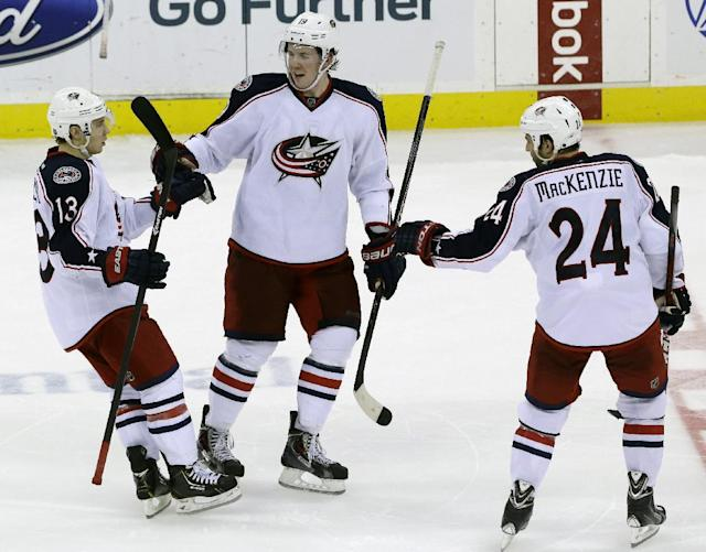 Columbus Blue Jackets right wing Cam Atkinson, left, is congratulated by teammates Ryan Johansen, center, and Derek MacKenzie after Atkinson scored a goal on New Jersey Devils goalie Martin Brodeur during a shootout in an NHL hockey game, Friday, Dec. 27, 2013, in Newark, N.J. The Blue Jackets won 2-1. (AP Photo/Julio Cortez)