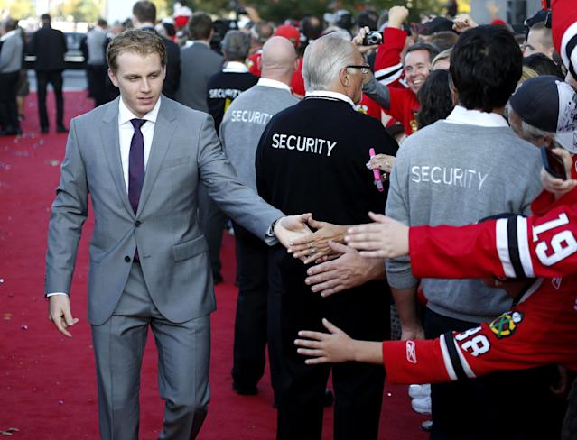 Chicago Blackhawks right wing Patrick Kane walks the red carpet greeting fans outside the United Center as the team arrives for their season-opening NHL hockey game against the Washington Capitals Tuesday, Oct. 1, 2013, in Chicago. (AP Photo/Charles Rex Arbogast)