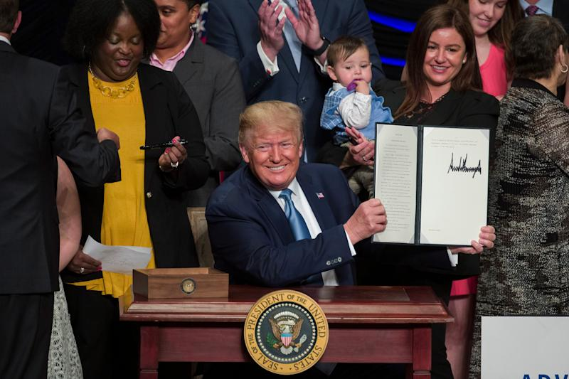President Donald Trump holds up a signed executive order about kidney health at the Ronald Reagan Building and International Trade Center, Wednesday, July 10, 2019, in Washington.