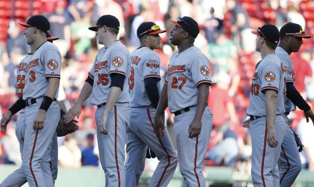 The Baltimore Orioles, including Ryan Flaherty (3), Brad Brach (35) Manny Machado (13), Delmon Young (27) and Nick Hundley (40) celebrate after defeating the Boston Red Sox 7-6 in the twelfth inning of a baseball game in Boston, Sunday, July 6, 2014. (AP Photo/Michael Dwyer)