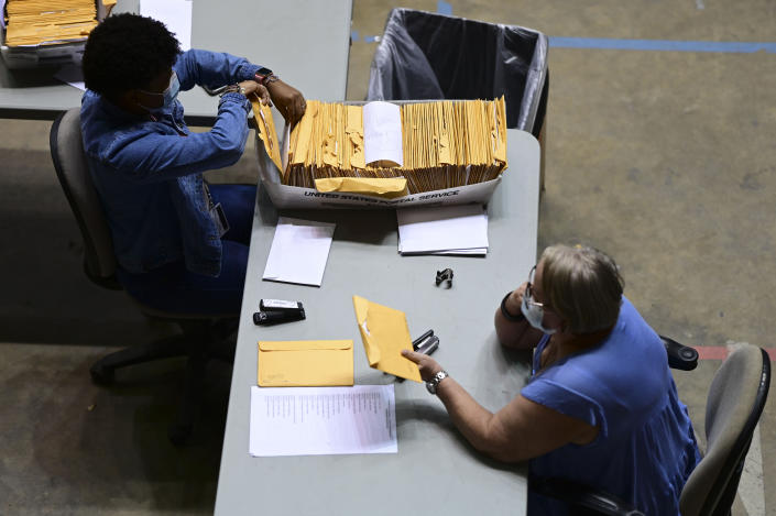 Officials count early votes at the Roberto Clemente Coliseum where social distancing is possible amid the COVID-19 pandemic, during general elections in San Juan, Puerto Rico, Tuesday, Nov. 3, 2020. In addition to electing a governor, Puerto Ricans are voting in a nonbinding referendum on statehood. (AP Photo/Carlos Giusti)