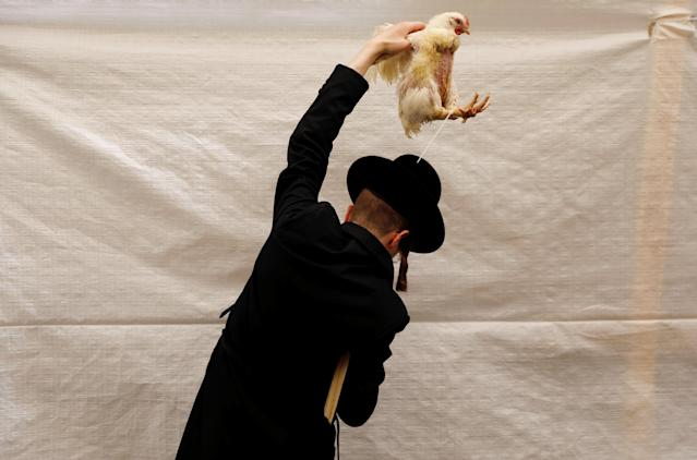 <p>An ultra-Orthodox Jewish man holds a chicken as he performs the Kaparot ritual, where white chickens are slaughtered as a symbolic gesture of atonement, ahead of Yom Kippur, the Jewish Day of Atonement, in Jerusalem's Mea Shearim neighborhood, Sept. 27, 2017. (Photo: Ronen Zvulun/Reuters) </p>