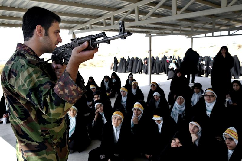 In this Thursday, Aug. 22, 2013 photo, a trainer of the Basij paramilitary militia shows female Basij members how to use an AK-47 rifle during a training session in Tehran, Iran. Authorities created the Basij, which means mobilization in Persian, just after the country's 1979 Islamic Republic. It is part of Iran's powerful Revolutionary Guard. (AP Photo/Ebrahim Noroozi)