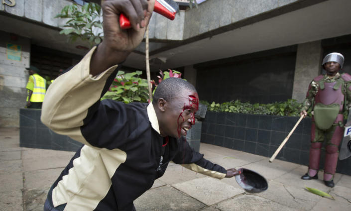 An opposition supporter with a head wound crawls past riot police, begging them not to beat him, during a protest in downtown Nairobi, Kenya, May 16, 2016. Kenyan police have tear-gassed and beaten opposition supporters during a protest demanding the disbandment of the electoral authority over alleged bias and corruption. (AP Photo/Ben Curtis)