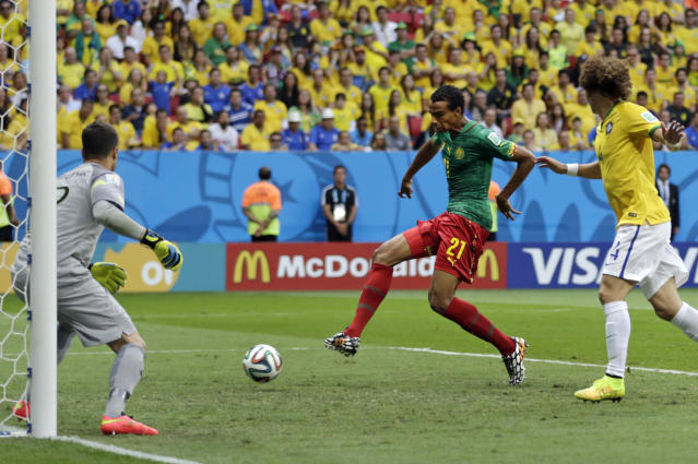Cameroon's Joel Matip, center, scores his side's first goal during the group A World Cup soccer match between Cameroon and Brazil at the Estadio Nacional in Brasilia, Brazil, Monday, June 23, 2014. (AP Photo/Dolores Ochoa)