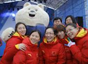 Members of the Chinese Olympic team pose with an Olympic mascot after a welcoming ceremony before the 2014 Winter Olympics, Wednesday, Feb. 5, 2014, in Sochi, Russia. (AP Photo/Vadim Ghirda)