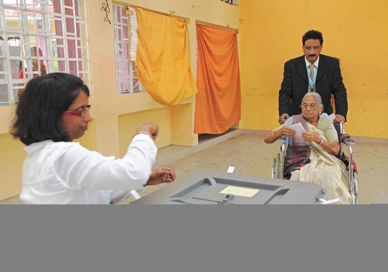 An elderly woman casts her vote at a polling station in Port Louis on December 10, 2014 (AFP Photo/Nicholas Larche)