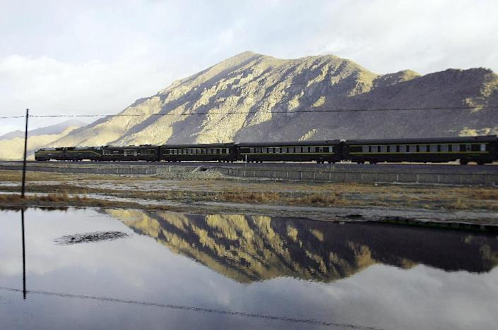 A train passes high peaks as it leaves the Tibetan capital Lhasa on its way to Beijing (AFP Photo/Peter Parks)