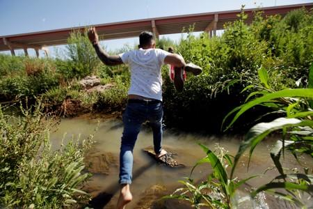 FILE PHOTO: A migrant from Cuba is seen on the banks of the Rio Bravo river as he crosses illegally into the United States to turn himself in to request asylum in El Paso, Texas, as seen from Ciudad Juarez