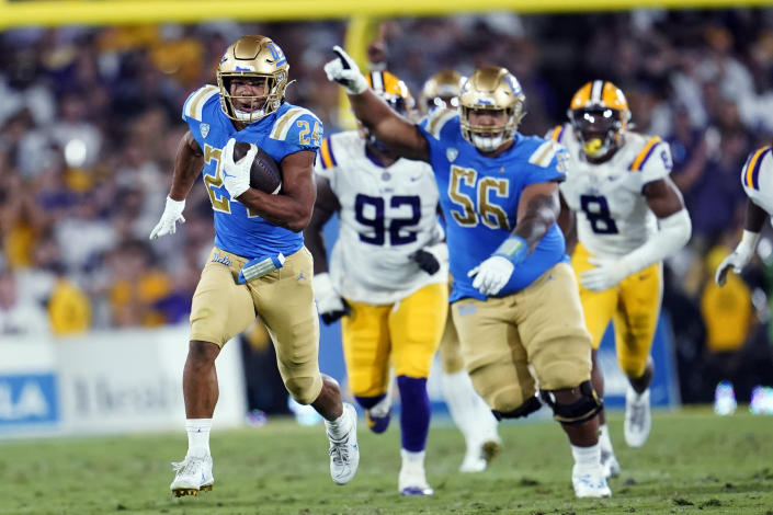 UCLA running back Zach Charbonnet, left, carries against LSU during the second half of an NCAA college football game Saturday, Sept. 4, 2021, in Pasadena, Calif. (AP Photo/Marcio Jose Sanchez)