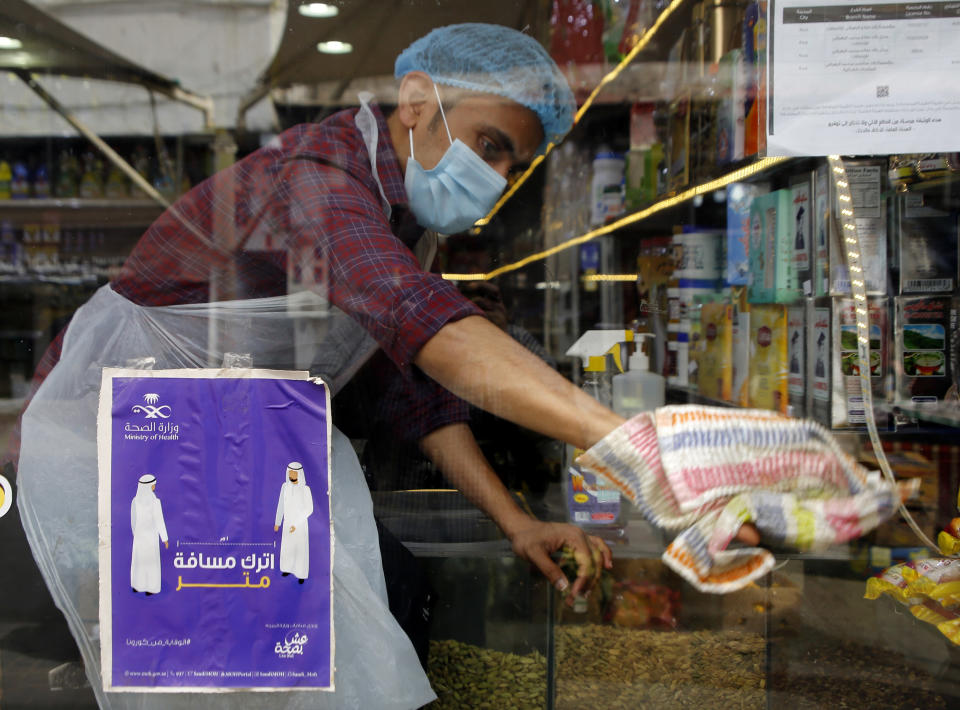 "A worker wearing a face mask to help curb the spread of the coronavirus, wipes his shop window behind a poster emphasizing an enhanced social distancing campaign at a popular market in Jiddah, Saudi Arabia, Thursday, Dec. 17, 2020. The Arabic reads, ""leave one meter distance."" (AP Photo/Amr Nabil)"