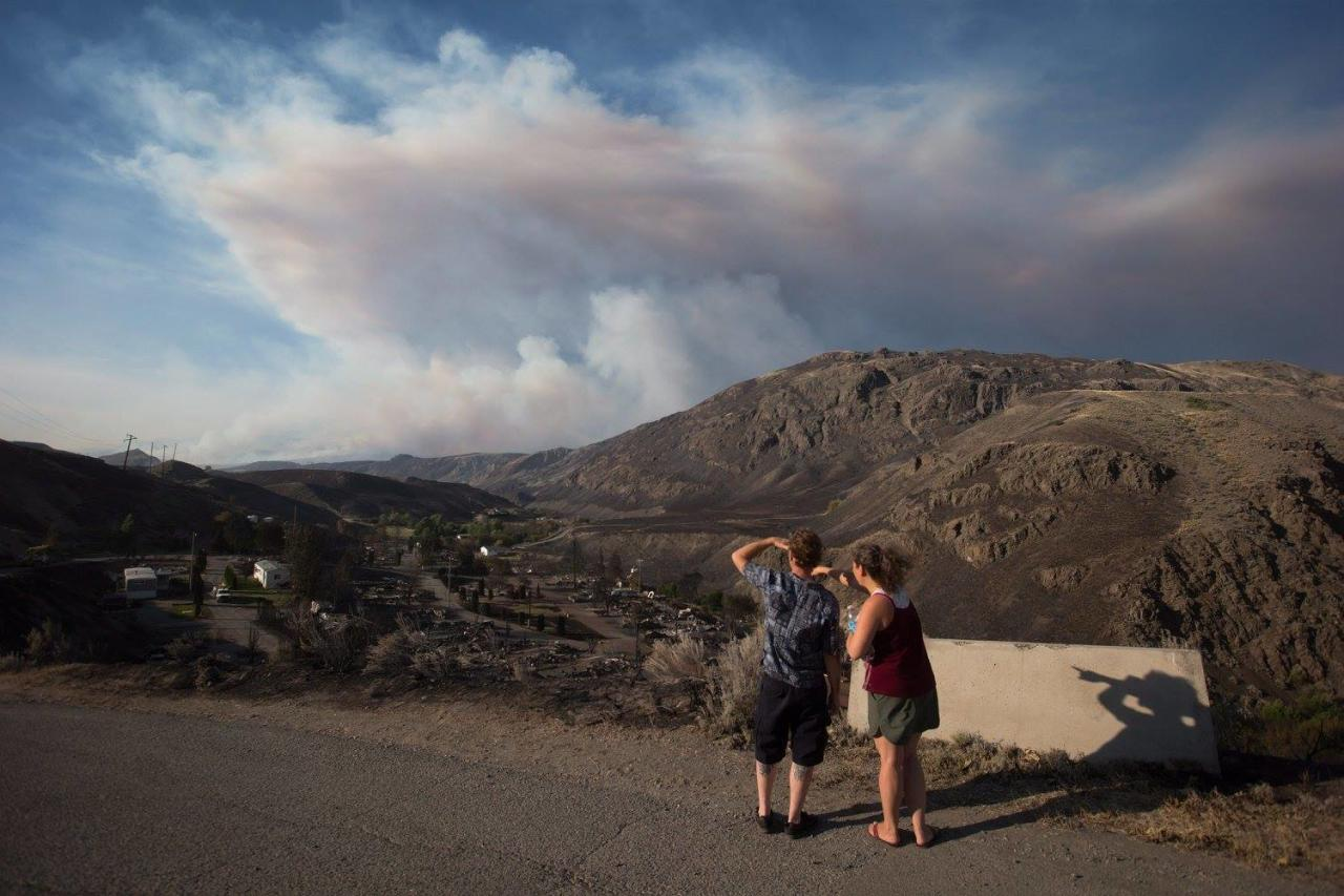 <p>Ashcroft residents stop to view the remains of mobile homes destroyed by wildfire in Boston Flats, B.C., as a fire burns in the distance. Photo from The Canadian Press </p>