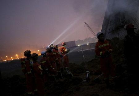 Firefighters use flashlights to search for survivors among the debris of collapsed buildings after a landslide hit an industrial park in Shenzhen, Guangzhou, China, December 20, 2015. REUTERS/Tyrone Siu