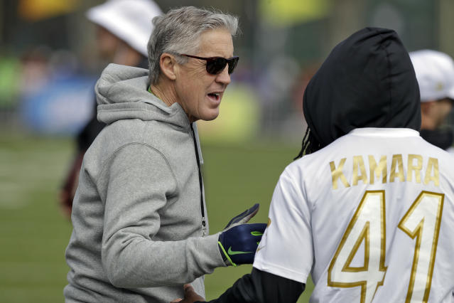 NFC head coach Pete Carroll, of the Seattle Seahawks, talks to running back Alvin Kamara, of the New Orleans Saints, during a practice for the NFL Pro Bowl football game Wednesday, Jan. 22, 2020, in Kissimmee, Fla. (AP Photo/Chris O'Meara)