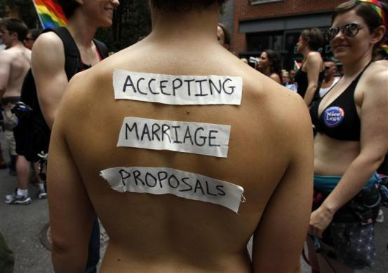 A woman wears a sign on her back which reads, 'Accepting Marriage Proposals' during the Gay Pride Parade in New York June 26, 2011.