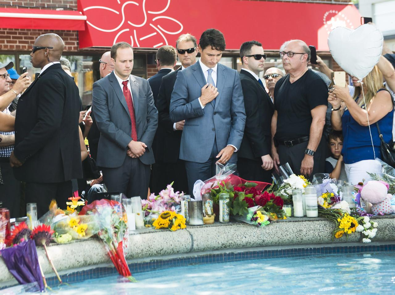 <p>Prime Minister Justin Trudeau pays his respects after placing flowers at the fountain at the Alexander the Great Parkette, near where people were gunned down and injured from the recent Danforth shootings in Toronto on Monday, July 30, 2018. Photo from The Canadian Press. </p>