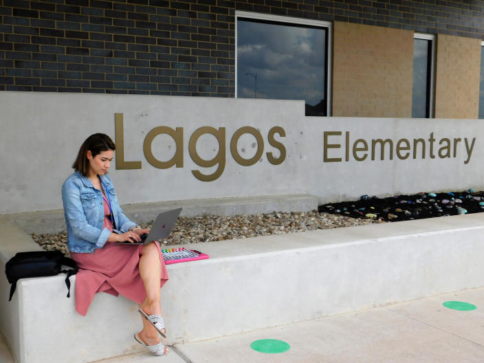 """First-year teacher Cindy Hipps sits outside of Lagos Elementary School, at Manor Independent School District campus east of Austin, Texas where she has taught first grade in a virtual and in-person hybrid classroom during the COVID-19 pandemic. Hipps said she was told she """"was introduced to the ring of fire of teaching."""" """"I feel like a superwoman now, like I can take on anything."""" (Acacia Coronado/Report for America via AP)"""