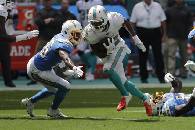 Los Angeles Chargers cornerback Casey Hayward (26) attempts to tackle Miami Dolphins running back Kenyan Drake (32), during the first half at an NFL football game, Sunday, Sept. 29, 2019, in Miami Gardens, Fla. AP Photo/Lynne Sladky)