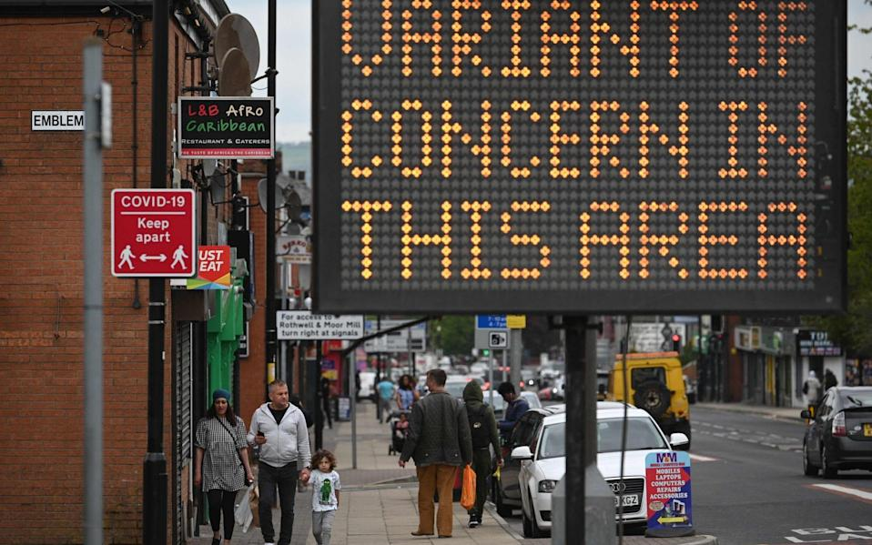 A public health digital board warns the public of a Covid-19 variant of concern affecting the community in Bolton, northwest England - AFP