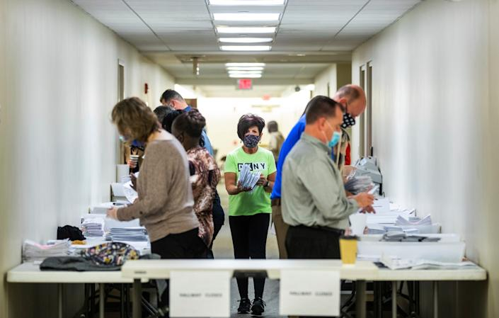 Jeri Shuits, center, office manager for the Beaver County Board of Elections, walks between election workers preparing ballots for counting in the basement of the Beaver County Courthouse on Wednesday, Nov. 4, 2020, in Beaver, Pa.