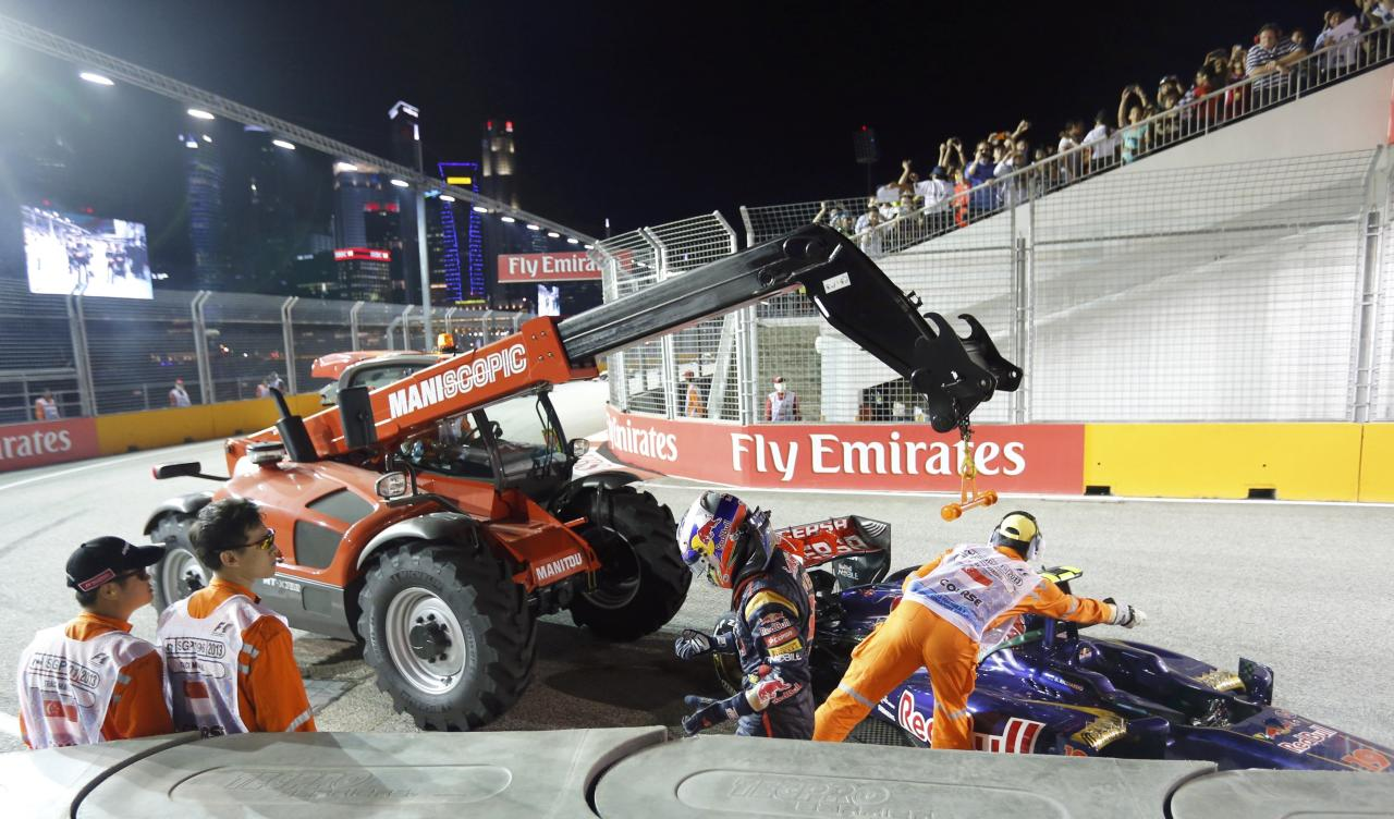 Toro Rosso Formula One driver Daniel Ricciardo of Australia walks away from his crashed car as it is recovered during the Singapore F1 Grand Prix at the Marina Bay street circuit in Singapore September 22, 2013. REUTERS/Natashia Lee (SINGAPORE - Tags: SPORT MOTORSPORT F1)