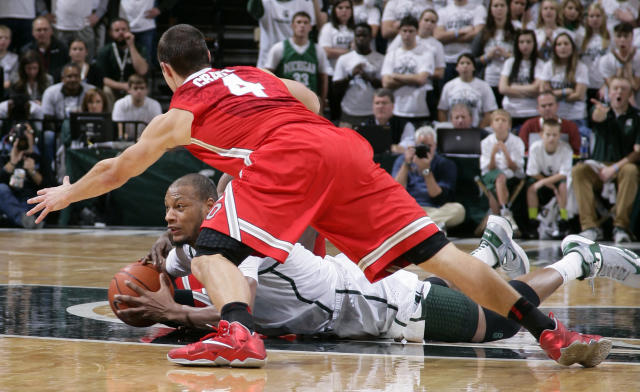 Michigan State's Adreian Payne, center, and Ohio State's Aaron Craft (4) and Shannon Scott, obscured, wrestle for the ball during the second half of an NCAA college basketball game, Tuesday, Jan. 7, 2014, in East Lansing, Mich. Michigan State won 72-68 in overtime. (AP Photo/Al Goldis)