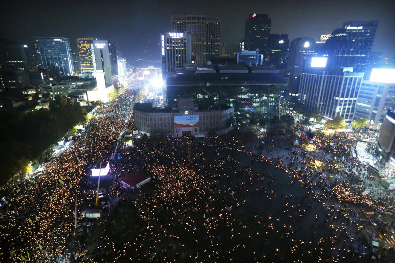 FILE - In this Nov. 12, 2016, file photo, people holding candle lights stage a rally calling for South Korean President Park Geun-hye to step down in Seoul, South Korea. South Korean President Moon Jae-in's office said Tuesday, July 10, 2018, that Moon has ordered an investigation into an allegation that the military drew up a plan to mobilize troops if protests worsened over the fate of his impeached predecessor last year. (AP Photo/Ahn Young-joon, File)