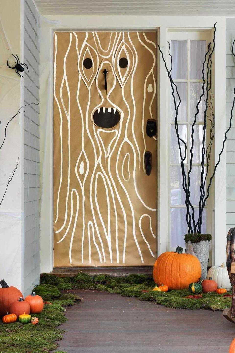 <p>Trick out your front porch with a layer of moss, spiderwebs and critters—plus a menacing tree trunk on the door. <strong><br></strong></p><p><strong>Make the Doorway:</strong> Use painter's tape to attach brown kraft paper to your door, cutting slits for the handle and knocker. Cut eyes and a mouth out of black construction paper; tape to kraft paper with double-sided tape. For the wood grain: Take white craft paint and draw curved lines first around the facial features, then vertically on the door. Place preserved green moss along the edges of your front steps or porch. Top with pumpkins.</p>