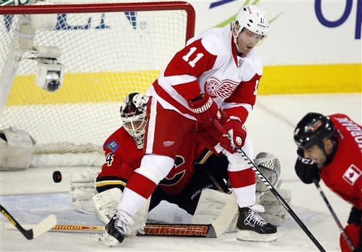 Detroit Red Wings' Daniel Cleary, right, tries to deflect the puck past Calgary Flames goalie Miikka Kiprusoff, of Finland, during the first period of their NHL hockey game in Calgary, Alberta, Wednesday, March 13, 2013. (AP Photo/The Canadian Press, Jeff McIntosh)