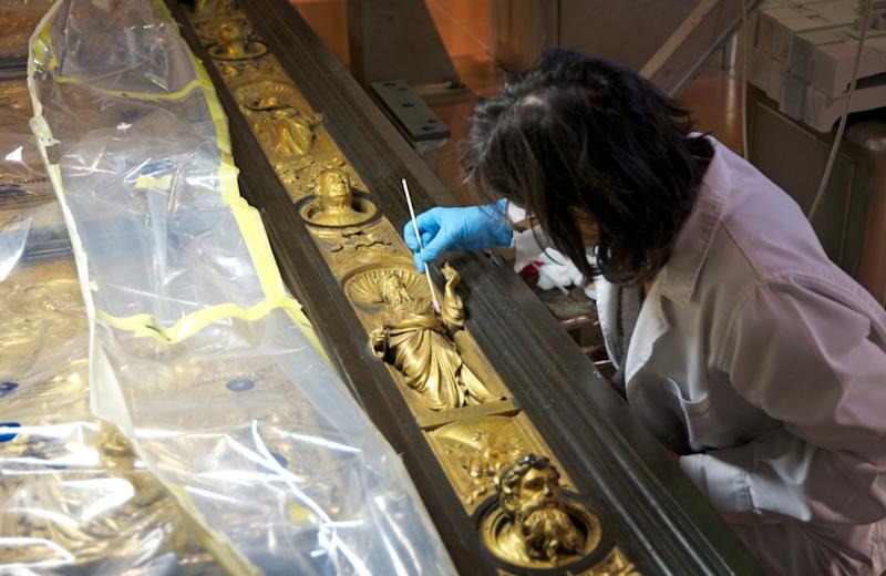 "In this undated photo provided by the Opera di Santa Maria del Fiore, a woman restores the original panel of the ""Door of Paradise"" in Florence, Italy. The original gilded bronze door, so splendid it was dubbed the ""Door of Paradise"" by Michelangelo, will be seen again in Florence after 27 years of restoration to remove damage by pollution, vandalism and the wear and tear of centuries. But Lorenzo Ghiberti's 15th-century door won't be going back in its place on the baptistry of Florence's duomo, or cathedral. Starting in September, it will go on display in a Florence museum, Museo dell'Opera di Santa Maria del Fiore, to preserve it from renewed damage. (AP Photo/Nicolò Orsi Battaglini, Opera di Santa Maria del Fiore)"