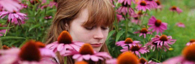 woman sitting in field of pink flowers looking melancholy