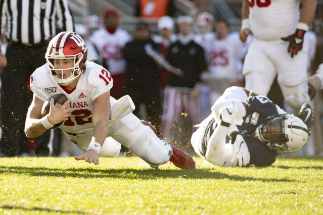 Indiana quarterback Peyton Ramsey (12) dives toward the end zone as he slips the grasp of Penn State linebacker Ellis Brooks (13) in the fourth quarter of an NCAA college football game in State College, Pa., on Saturday, Nov.16, 2019. Penn State defeated 34-27. (AP Photo/Barry Reeger)