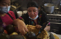 Natalia Méndez, right, goes through a basket of ingredients, as she prepare meals in the kitchen of La Morada, an award winning Mexican restaurant she co-owns with her family in South Bronx, Wednesday Oct. 28, 2020, in New York. After recovering from COVID-19 symptoms, the family raised funds to reopen the restaurant, which they also turned into a soup kitchen serving 650 meals daily. (AP Photo/Bebeto Matthews)