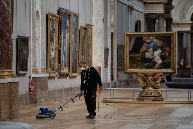 An employee cleaning the floor of a room of the Musee du Louvre in Paris