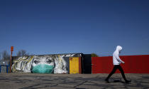 A man walks by a street art mural, depicting a healthcare worker in a face mask by Belgian street artist CAZ, during a partial lockdown against the spread of COVID-19 in Wetteren, Belgium, March 31, 2020. (AP Photo/Virginia Mayo)