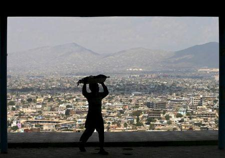Boy carries bread on his head to sell on a hilltop overlooking Kabul