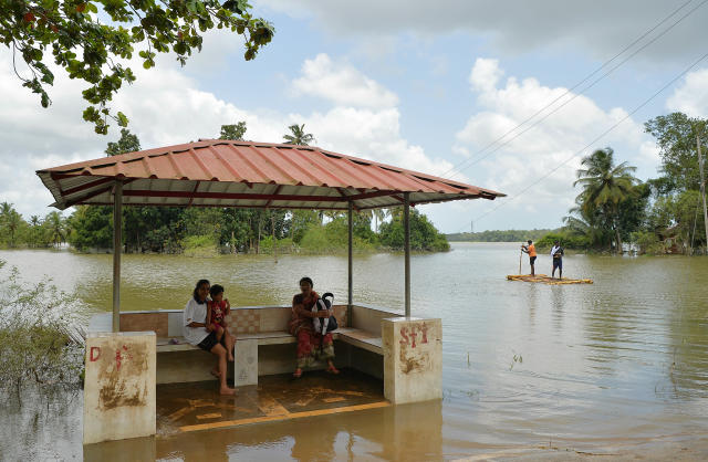 <p>Residents of Pandanad sit in a bus stand surrounded by flood waters from the overflowing Pampa river while raft is pictured near them transported people in Pandanad of Alappuzha District in the south Indian state of Kerala on August 21, 2018. – More than one million people have swarmed relief camps in India's Kerala state to escape devastating monsoon floods that have killed more than 410 people, officials said Tuesday as a huge international aid operation gathered pace. (Photo by MANJUNATH KIRAN/AFP/Getty Images) </p>