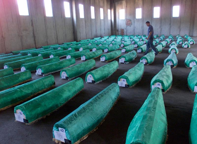 A Bosnian man looks at the identified bodies of 107 Srebrenica victims at the abandoned factory hangar in Potocari near Srebrenica, 75 kms southeast of Tuzla, on Friday, Sept. 19, 2003. The bodies of 107 victims that have been identified by DNA analysis will be buried on Saturday, Sept. 30. At the invitation of families of the victims, fromer US President Bill Clinton will participate in the dedication of the Srebenica-Potocari Memorial and Cemetery, which pays tribute to those who were massacred there in 1995. (AP Photo/Amel Emric) (Photo: ASSOCIATED PRESS)