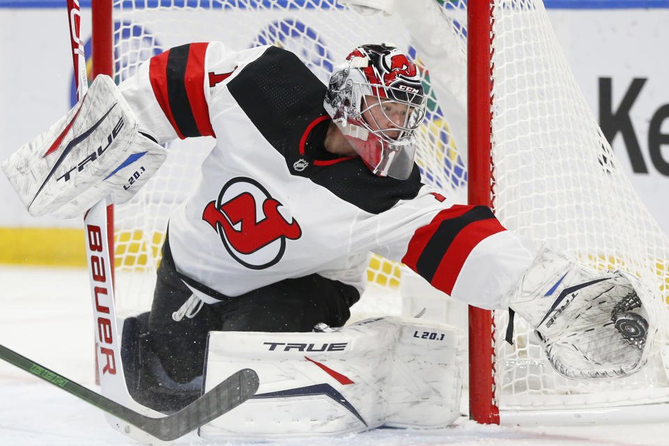 New Jersey Devils goalie Eric Comrie (1) makes a save during the second period of an NHL hockey game against the Buffalo Sabres, Sunday, Jan. 31, 2021, in Buffalo, N.Y. (AP Photo/Jeffrey T. Barnes)