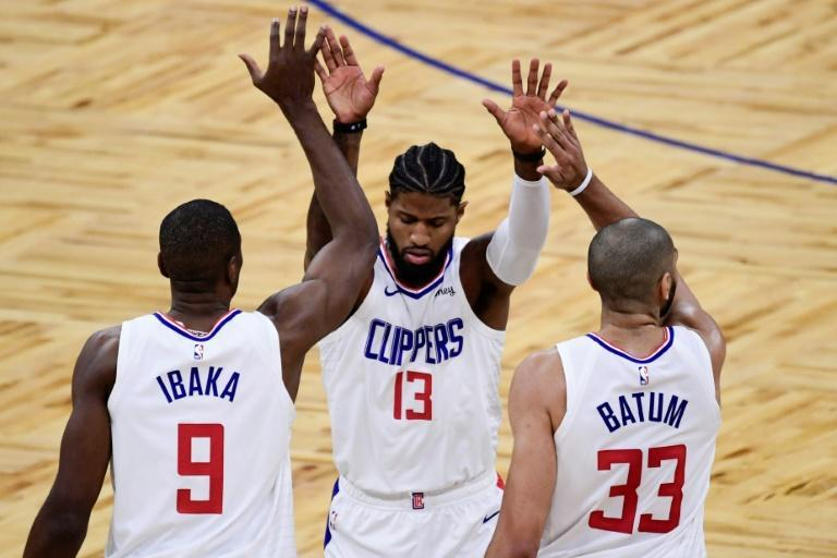 Los Angeles Clippers all-star Paul George, centre, celebrates with teammates Serge Ibaka and Nicolas Batum during the first quarter against the Orlando Magic at Amway Center arena