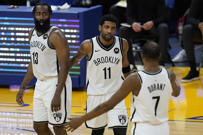 Brooklyn Nets guard Kyrie Irving, middle, gathers with guard James Harden (13) and forward Kevin Durant (7) during the second half of the team's NBA basketball game against the Golden State Warriors in San Francisco, Saturday, Feb. 13, 2021. (AP Photo/Jeff Chiu)