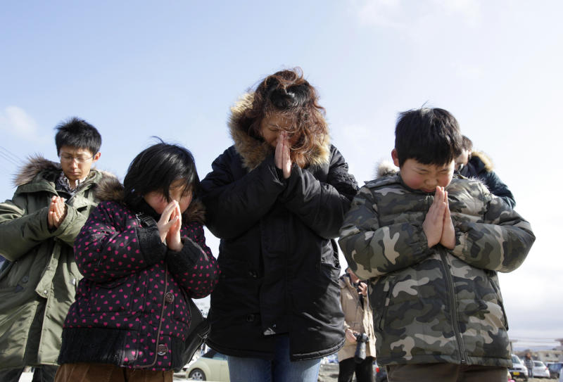 A family observes a moment of silence in front of what is left of a disaster control center in an area devastated by the March 11, 2011 earthquake and tsunami, in Minamisanriku, Miyagi prefecture, Japan, Sunday, March 11, 2012. Through silence and prayers, people across Japan on Sunday remembered the massive earthquake and tsunami that struck the nation one year ago, killing just over 19,000 people and unleashing the world's worst nuclear crisis in a quarter century. (AP Photo/Shizuo Kambayashi)