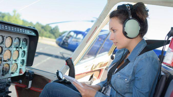 helicopter pilot reading a manual while sitting in cockpit