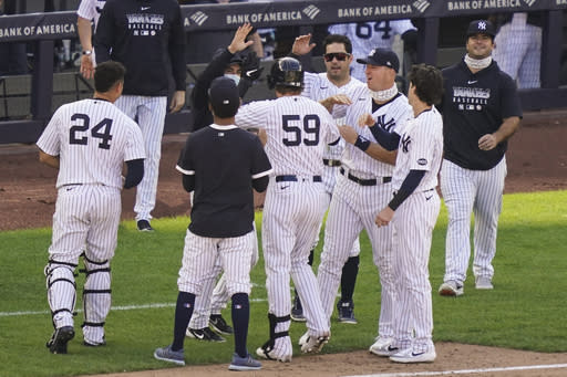 New York Yankees' Luke Voit (59) celebrates with teammates after hitting a walkoff RBI sacrifice fly off Baltimore Orioles relief pitcher Hunter Harvey in the 10th inning of a baseball game, Saturday, Sept. 12, 2020, in New York. (AP Photo/John Minchillo)