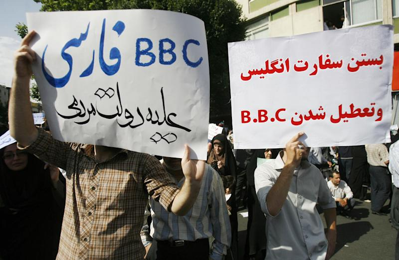 """Supporters of President Mahmoud Ahmadinejad hold up placards against the British media during a rally in Tehran's Vali Asr Square on June 16, 2009. The rally, called by the Islamic Propagation Council, was staged at the same time as a rival gathering by supporters of defeated candidate Mir Hossein Mousavi. Farsi slogans read: """"Closing the British Embassy and BBC,"""" right, and """"Persian BBC against the Iranian government."""" (Photo: ALIREZA SOTAKBAR/AFP/Getty Images)"""