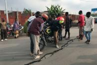 People look at a crack on the road caused by earth tremors as aftershocks following the eruption of Mount Nyiragongo volcano near Goma